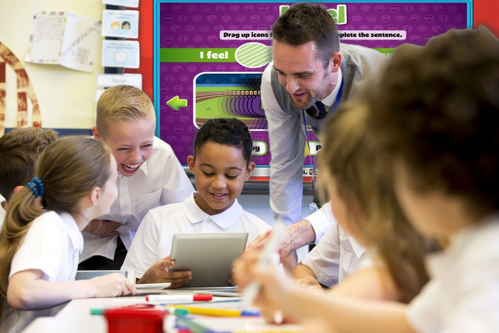 Teacher engaging with students on an iPad with Interactive Whiteboard behind him.