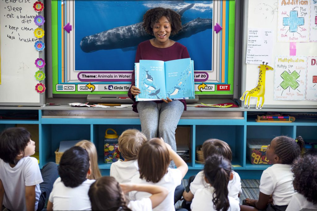 PreK teachers sits and reads to students about whales while an interactive whiteboards shows whales in the background.