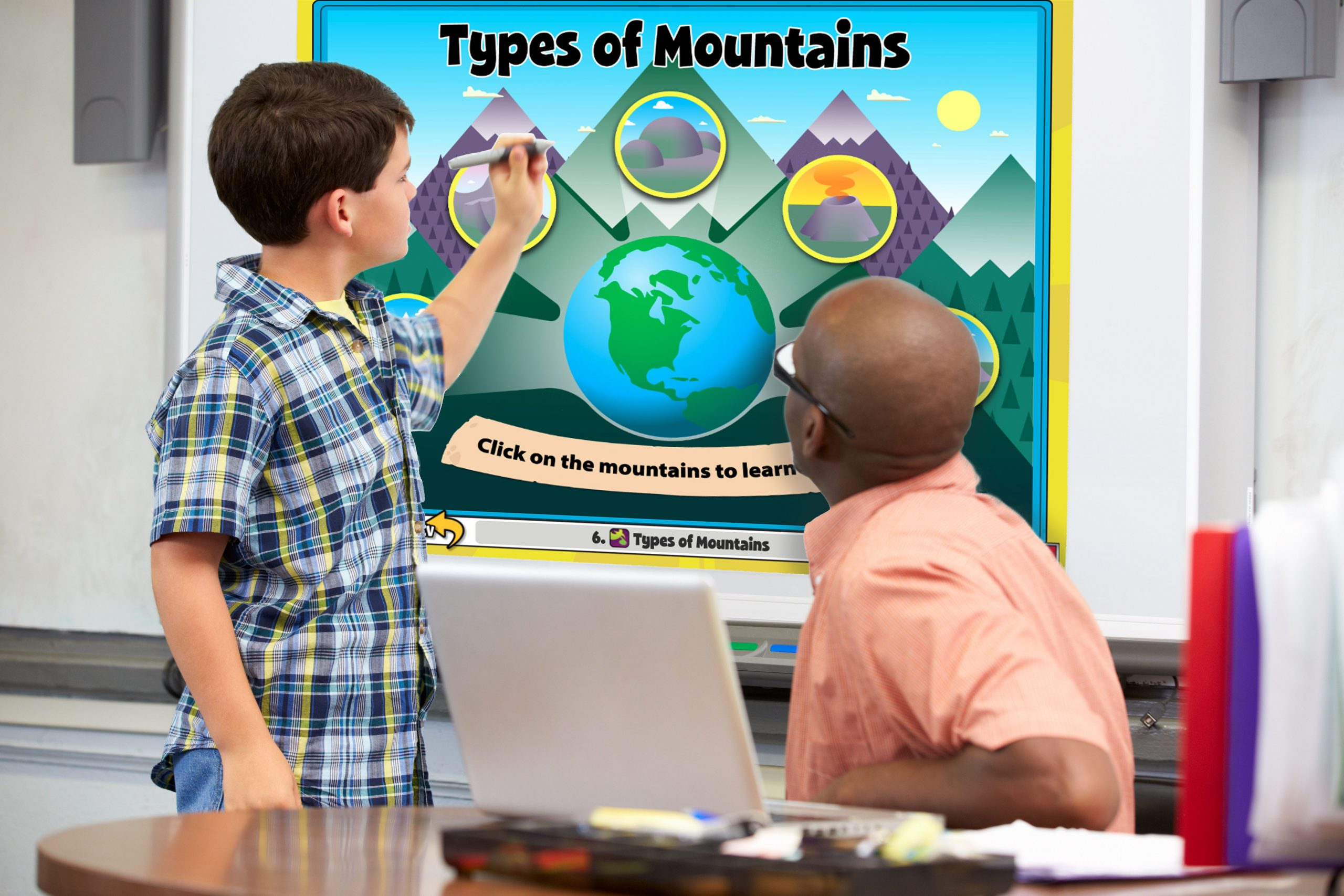Student and Teacher work together on whiteboard activity involving types of mountains.