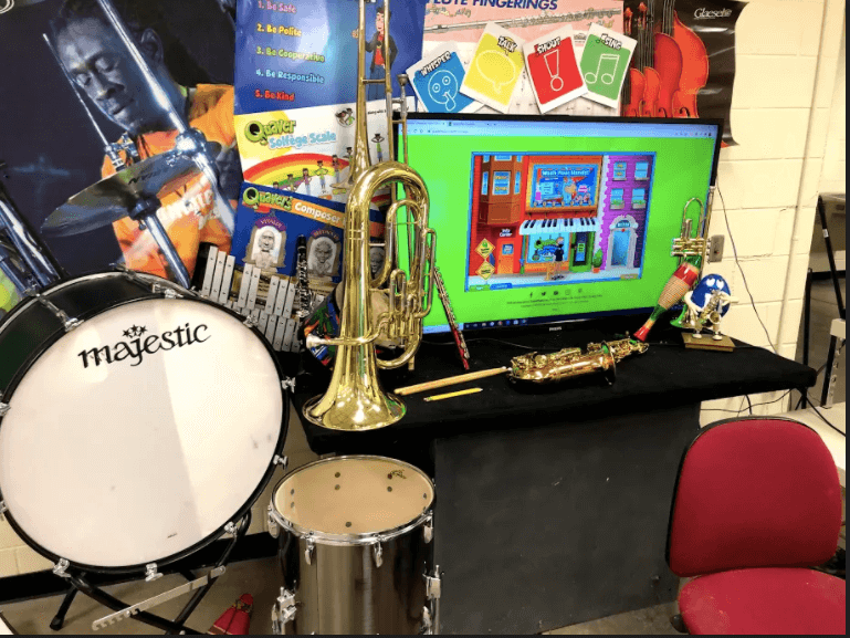 Image of Dan Brennan's virtual classroom background with instruments, posters, and a TV
