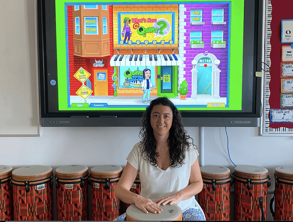 Image of Quaver Music teacher Mari Carmen sitting in her classroom with a drum and Quaver on the screen behind her