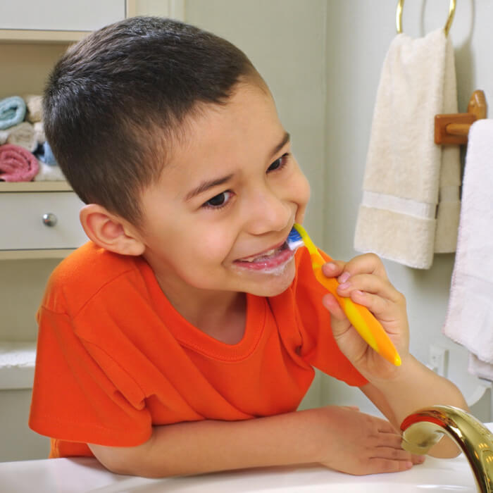 Young child brushing teeth while looking in a bathroom mirror