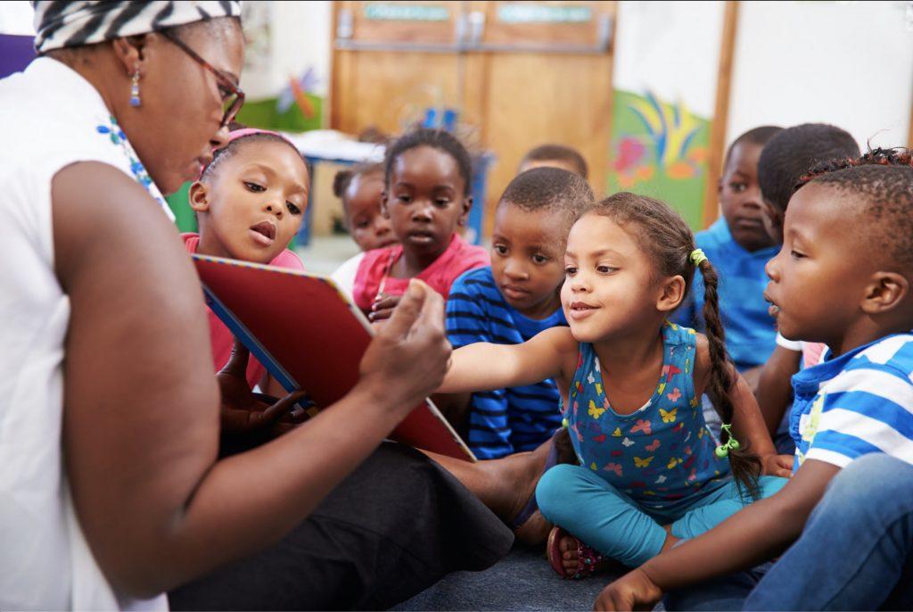 PreK Students Reading with Teacher on the Floor
